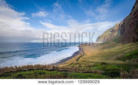 Madeira island wild bay Calhau das Achadas, popular viewing and hiking spot. Atlantic ocean, mountains and fields in sunny january day.