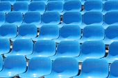 several rows of blue sunlit stadium seats poster