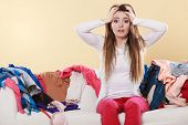 Desperate helpless woman sitting on sofa couch in messy living room with hands on head. Young girl surrounded by many stack of clothes. Disorder and mess at home. poster