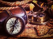 Travel geography navigation concept background -  vintage retro effect filtered hipster style image of old vintage retro compass with sundial, spyglass and rope on ancient world map poster