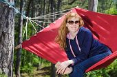 Young smiling girl in glasses enjoy in red hammock in forest. Redhead woman with freckles smile. Forest, mountains in the background. poster