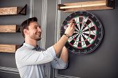Relief negativity. Cheerful content handsome smiling man standing near the wall and expressing gladness while playing darts poster
