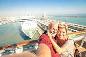 Senior happy couple taking selfie on ship at Barcelona harbour background - Mediterranean cruise travel tour - Active elderly concept with retired people around the world - Warm afternoon color tones poster