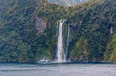 Milford Sound New Zealand - November 14 2014: The Milford Mariner Ship near high waterfall at Milford Sound Fjord New Zealand. poster