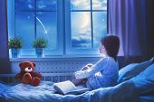 Cute child girl sitting at the window and looking at the stars. Girl making a wish by seeing a shooting star at bedtime night. poster