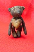 teddy bear handmade and cookie in the form of heart on a red background poster