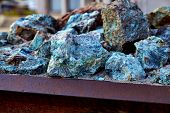 Chunks of copper ore mineral rocks in an iron barrel poster