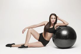 Portrait of young attractive woman doing exercises. Brunette with fit body exercising with fitness ball. Series of exercise poses.