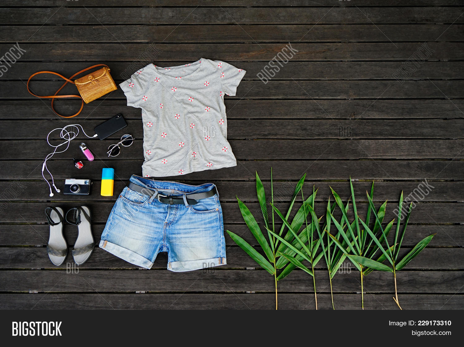3381102c7f85 Woman summer clothes collage flat lay isolated on dark wood background.  Feminine desk top view fashion accessories: t-shirt, shorts, sandals,  sunglasses, ...
