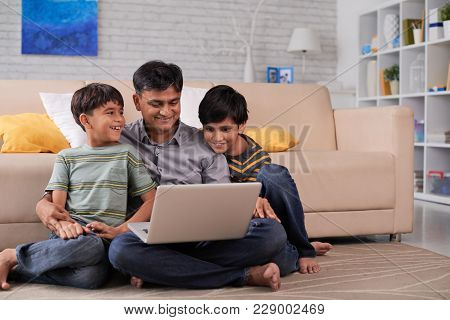 Smilng Indian Man Sitting On The Floor With Two Sons And Watcvhing Funny Videos On Laptop