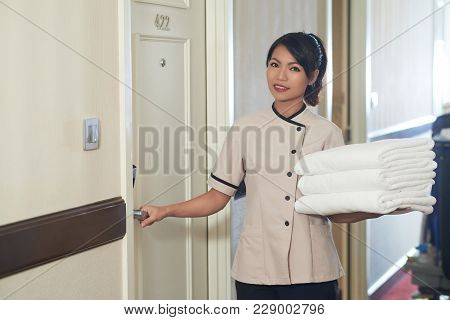 Beautiful Hotel Maid With Stack Of Clean White Towels