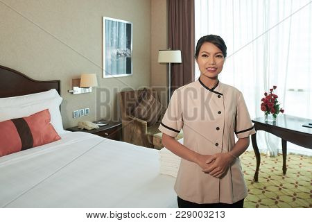 Smiling Young Asian Maid In Hotel Room Ready For Guests