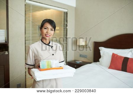 Smiling Spa Resort Maid Bringing Towels, Creams And Lotions To Guest Room