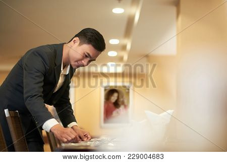 Catering Manager Checking Silverware On Restaurant Table
