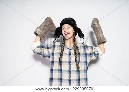Happy Laughing Russian Girl In A Warm Hat Holds A Winter Felt Boots
