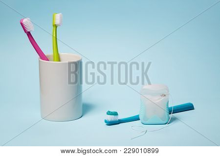 Dental Equipment. Colorful toothbrushes in mug and dental floss on light blue background. Copy space, studio shot.