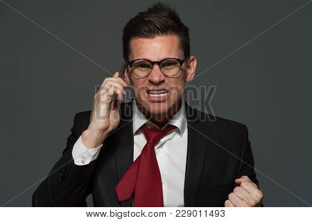 Stress At Work. An Upset Businessman Talks On The Phone About Ruptured Deal On Gray Background