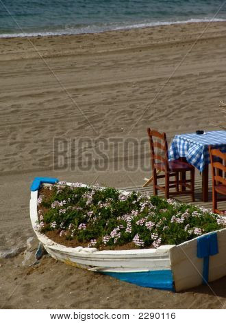 A Boat With Flowers Next To A Cafe On A Spanish Beach