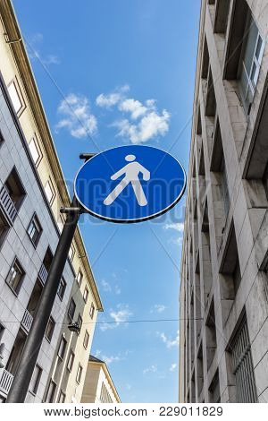 Blue And White Circular Road Sign. Pedestrian Zone. On The Sides Two Vintage Style Buildings. Blue S