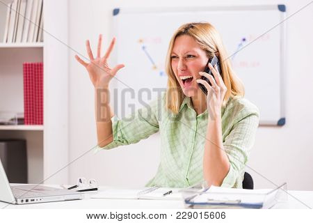 Businesswoman Is Working In Her Office. She Is Arguing On Phone.