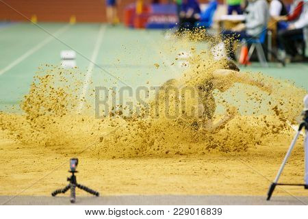 Sportsman Landing Into Sandpit On Training In Long Jump. Track And Field Competitions Concept Backgr