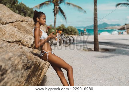 Side View Of Svelte Sexy Brazilian Girl Leaning On The Rock And Holding In Hands Fresh Coconut; Youn