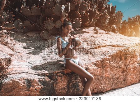 Smoking Hot Black Girl In Swimsuit Is Leaning On The Rock While Drinking Coco Water With Multiple Ca
