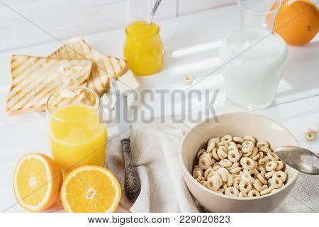 Delicious Healthy Breakfast.  Whole Grain Cereal Rings, Milk, Honey And Orange Juice On The White Ta