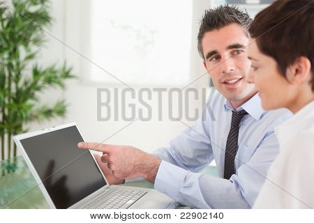 Manager pointing at something to his secretary on a laptop in an office