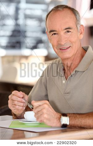 Middle-aged man drinking coffee on terrace