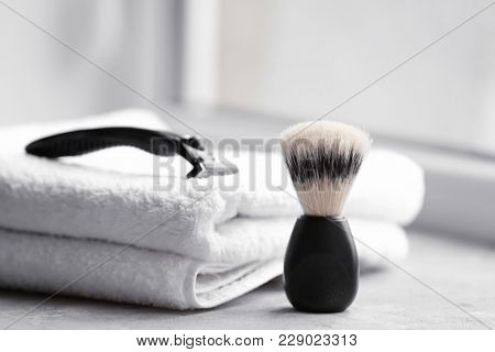 Shaving brush, towel and razor for man on table