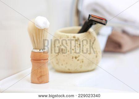 Shaving brush for man with foam on sink