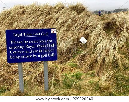 TROON, SCOTLAND - FEBRUARY 19, 2018: A sign advising the dangers to the public of entering The Royal Troon Golf Club course in Troon, South Ayrshire, Scotland, UK.