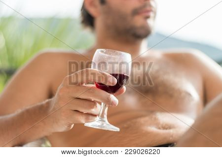 Young Relaxed Caucasian Man Holding A Dirty Glass Of Red Wine In The Balcony