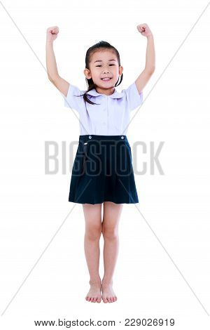 Full Body Of Preschool Child In Uniform With Her Hands Up And Smiling Happily. Cute Asian Girl Stand