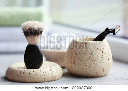 Shaving brush and razor for man on table