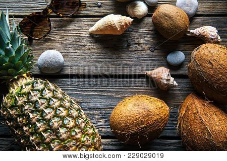 Composition Of Fresh Pineapple And Coconuts On Wooden Background A