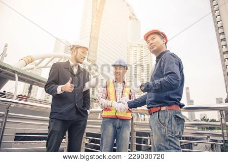 Engineers and businessmen collaborate to plan the building, Successful team with construction on sit