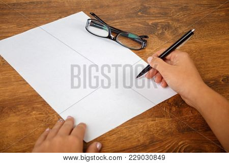 Signing A Contract Or Document, Writing An Essay, Right Female Hand Holding The Pen Above The Empty