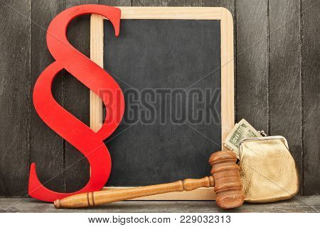 Business Law and Banking Law Concept with money and paragraph next to an empty chalkboard