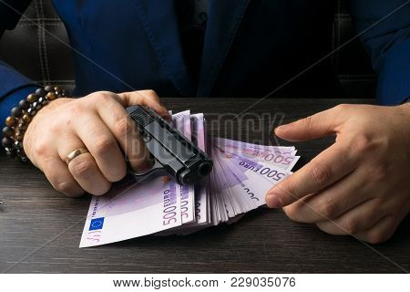 Money, Weapons Demonstrating The Concept Of A Bandit. Mans Hands. Terrorist Activity.
