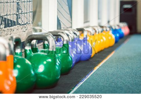 Close-up of metallic kettlebells of various weights and colors on the floor of a fitness club with modern equipment for functional training