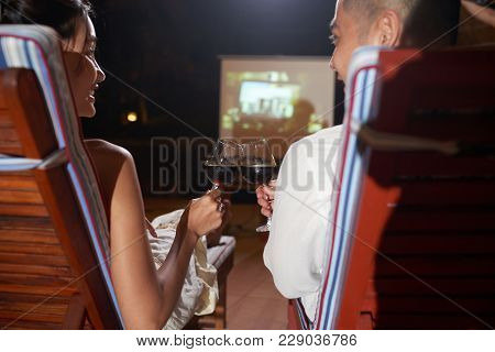 Back View Of Cheerful Asian Couple Toasting With Wine Glasses While Sitting On Cozy Deck Chairs And