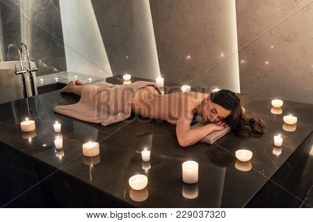Beautiful woman lying down on massage table surrounded by scented candles in luxury spa and wellness center
