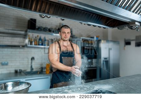 Chef Cook Bodybuilder Claps His Hands With Flour On The Kitchen Interior. Cooking Process