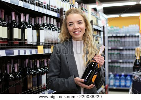 Young woman with bottle of alcohol drink in liquor shop. Small business owner