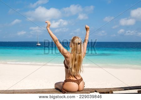 Beautiful Blonde Woman In The Knitted Brown Bikini Sitting On The Old Wooden Bench On The Lonely Bea