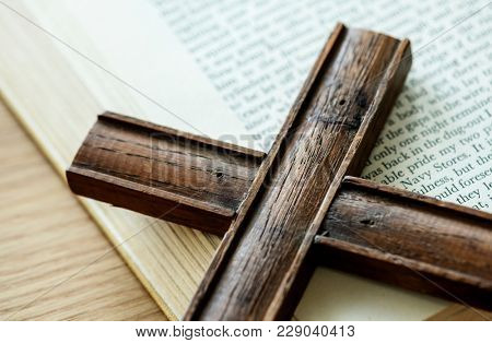 Closeup of wooden cross on bible book religion and belief concept