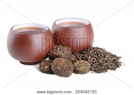 Cups Of Chinese Black Pu-erh Tea And Dried Tea Blocks On White Background