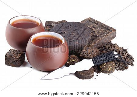 Cups Of Chinese Tea And Dried Pu-erh Tea Leaves With Special Knife On White Background